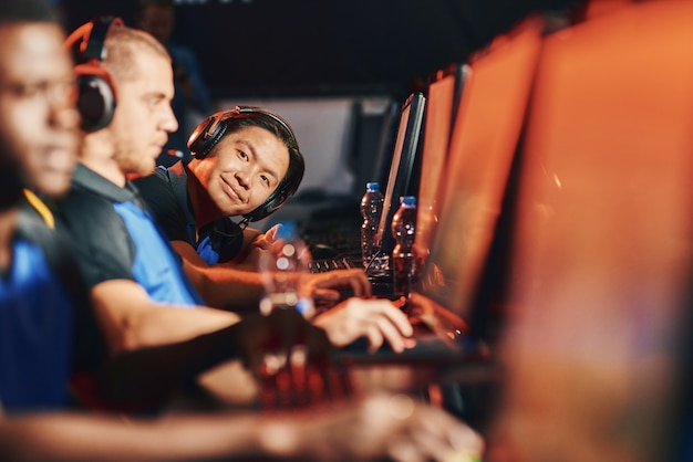 Jonge aziatische man, mannelijke cybersport-gamer die een koptelefoon draagt die naar de camera kijkt en glimlacht terwijl hij op een rij zit met andere teamleden voor pc-monitoren. esport-toernooiconcept