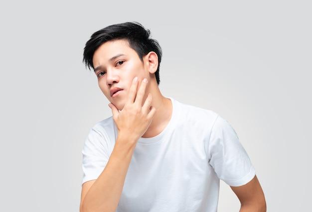 Jonge aziatische man met behulp van hand raakt zijn kin om zijn huid te controleren