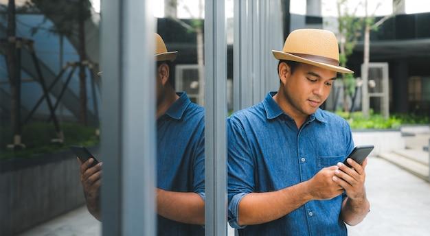 Jonge aziatische man met behulp van smartphone.