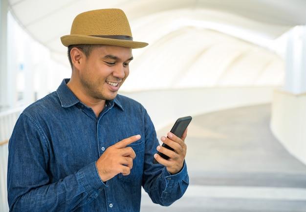 Jonge aziatische man met behulp van telefoon.