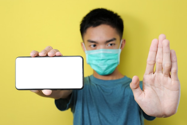 Jonge aziatische man met beschermmasker doet stopgebaar om te stoppen met delen hoax, nepnieuws, geïsoleerd op geel