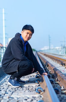 Jonge aziatische man met casual kleding met hand op spoorweg in ho chi minh city, vietnam