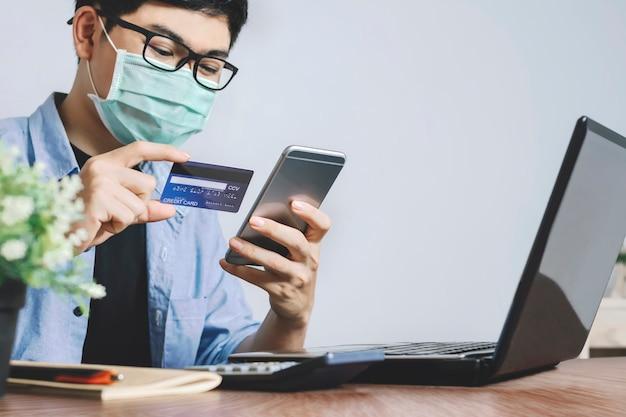 Jonge aziatische man met creditcard online betaling na online kopen, internet winkelen met kaart