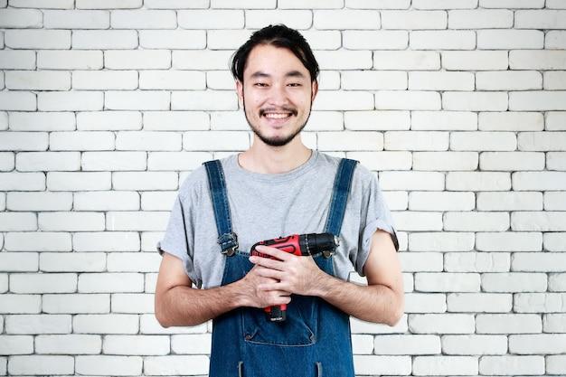 Jonge aziatische man met een boormachine die voor een witte bakstenen muur staat, lacht en kijkt naar de camera, concept voor thuis diy