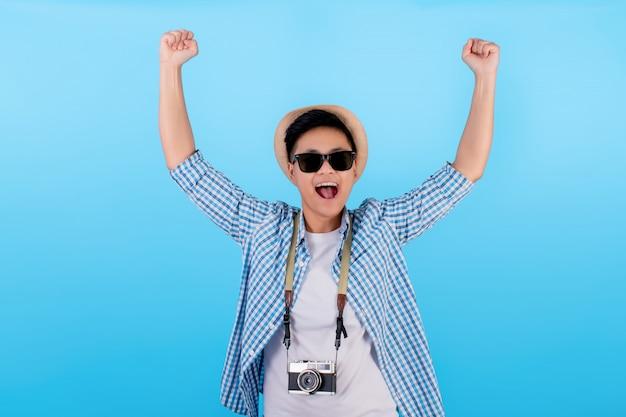Jonge aziatische man met een casual outfit houdt beide handen opgewonden en heft zijn vuist op met een lachend gezicht op een blauw