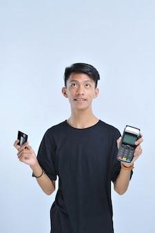 Jonge aziatische man met een creditcard / een debetkaart en een electronic data capture (edc)-machine voor gemakkelijke en snelle financiële transactie geïsoleerd over de grijze achtergrond