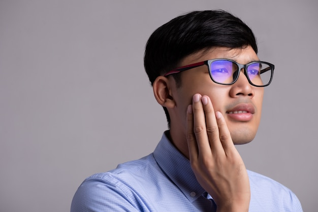 Jonge aziatische man met gevoelige tanden of kiespijn. gezondheidszorg concept.