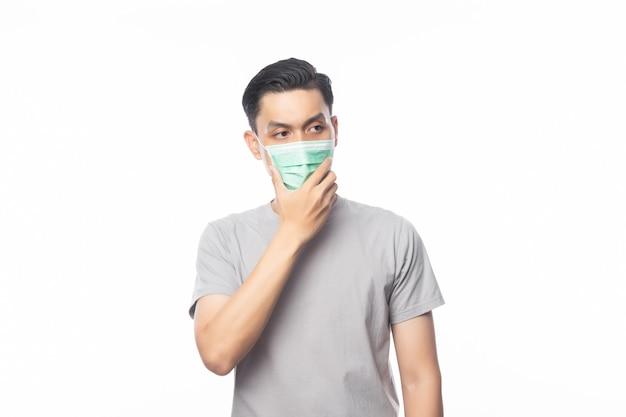 Jonge aziatische man met hygiënisch masker en denken om infectie, 2019-ncov of coronavirus te voorkomen. luchtwegaandoeningen zoals pm 2,5 vechten en griep geïsoleerd