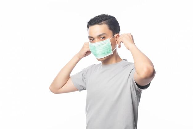 Jonge aziatische man met hygiënisch masker om infectie, 2019-ncov of coronavirus te voorkomen. luchtwegaandoeningen zoals pm 2,5 vechten en griep. studio shot geïsoleerd