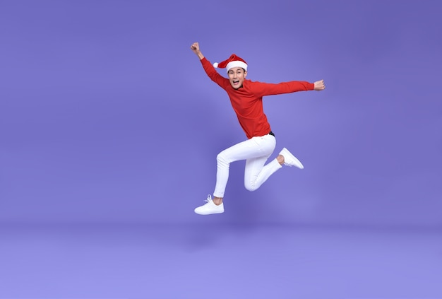 Jonge aziatische man met kerstmuts springen en lach gezicht