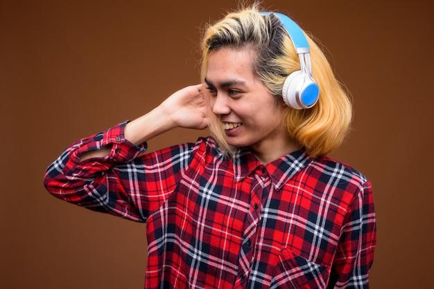 Jonge aziatische man met koptelefoon stijlvolle kleding dragen tegen bruine achtergrond