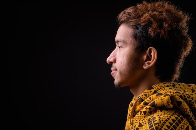 Jonge aziatische man met krullend haar en acne hoodie dragen tegen zwarte ruimte