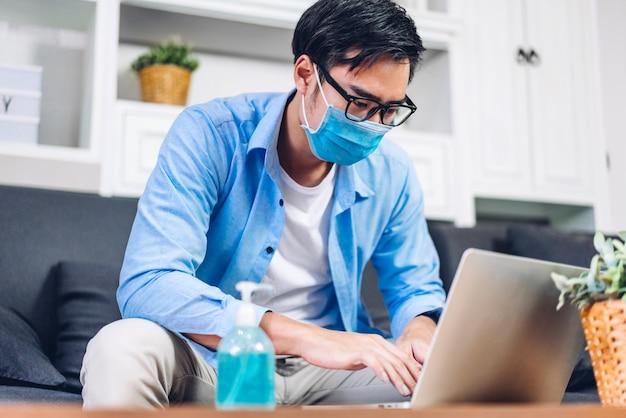 Jonge aziatische man met laptopcomputer werken en videoconferentie vergadering online chat in quarantaine voor coronavirus dragen van beschermend masker met sociale afstand thuis. werk vanuit huis concept