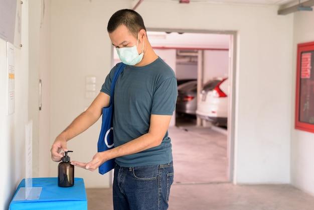 Jonge aziatische man met masker die handdesinfecterend middel gebruikt om verspreiding van het coronavirus te voorkomen