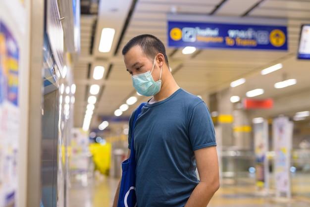 Jonge aziatische man met masker kaartje kopen bij het metrostation