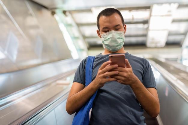 Jonge aziatische man met masker met behulp van telefoon tijdens het naar beneden gaan van de roltrap