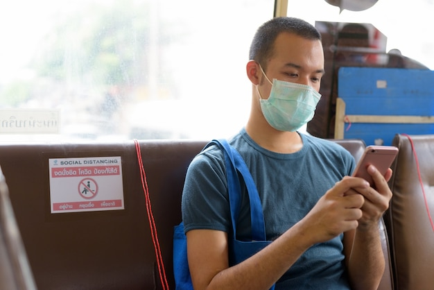 Jonge aziatische man met masker met behulp van telefoon zittend op de bus met afstand
