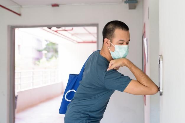 Jonge aziatische man met masker op liftknop met elleboog te drukken om verspreiding van het coronavirus te voorkomen