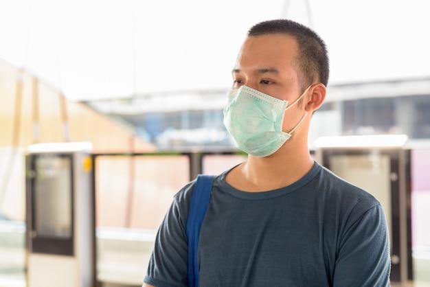 Jonge aziatische man met masker voor bescherming tegen uitbraak van coronavirus, denken en wachten op het skytrain-station
