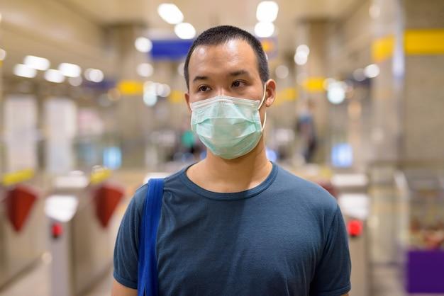 Jonge aziatische man met masker voor bescherming tegen uitbraak van coronavirus op het metrostation