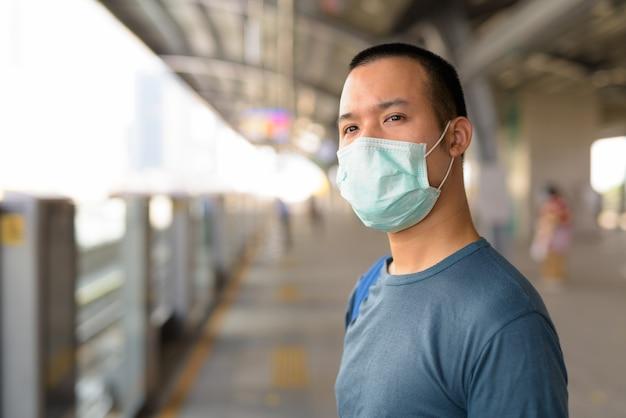 Jonge aziatische man met masker voor bescherming tegen uitbraak van coronavirus te wachten op het sky train station