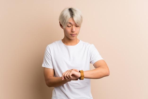 Jonge aziatische man met polshorloge