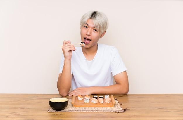 Jonge aziatische man met sushi in een tafel