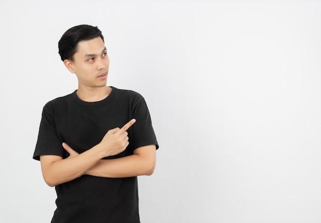 Jonge aziatische man met zwart shirt wijst naar de zijkant met een vinger om een product of een idee te presenteren terwijl hij zich verassend verheugt