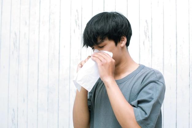 Jonge aziatische man niezen in papieren zakdoekje thuis