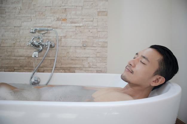 Jonge aziatische man ontspannen en spa in badkuip.
