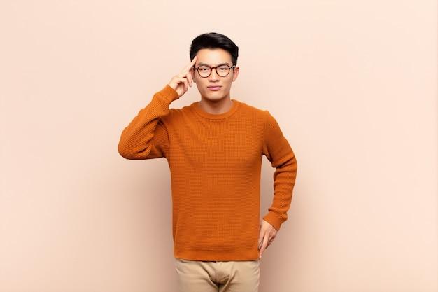 Jonge aziatische man op zoek verrast, met open mond, geschokt, het realiseren van een nieuwe gedachte