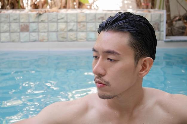 Jonge aziatische man permanent in zwembad op vakantie.