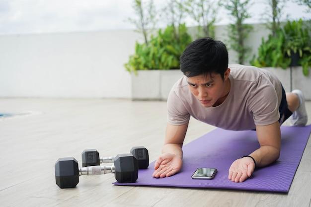 Jonge aziatische man plank oefening op mat om kracht kernspier te bouwen