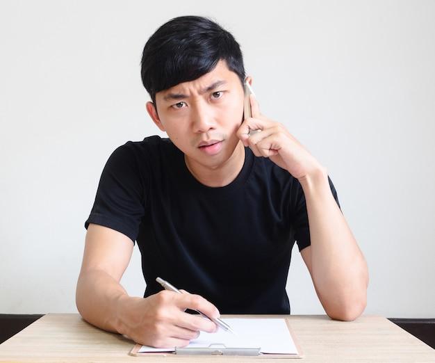 Jonge aziatische man praat met een serieus gezicht met de pen en het klembord op het bureau