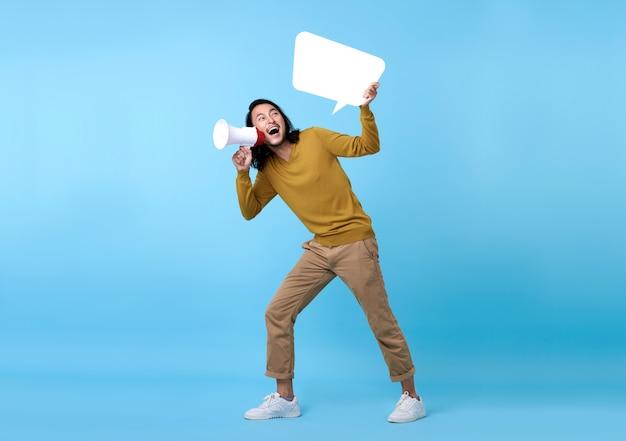 Jonge aziatische man schreeuwen in megafoon en houdt tekstballon geïsoleerd op blauwe ruimte.