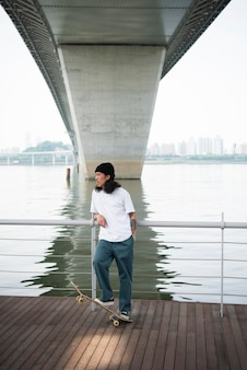 Jonge aziatische man skateboarden in de stad buiten