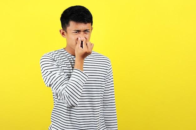 Jonge aziatische man sluit zijn neus voor slechte geur, geïsoleerd op gele achtergrond