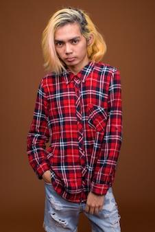Jonge aziatische man stijlvolle kleding dragen tegen bruine achtergrond