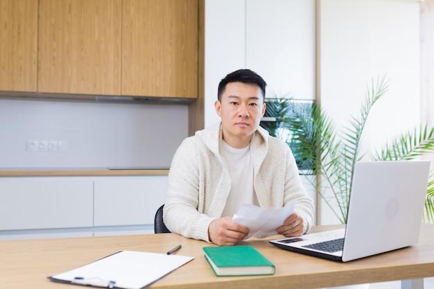 Jonge aziatische man telt rekeningen bankcheques leningen of nutsvoorzieningen terwijl hij thuis zit