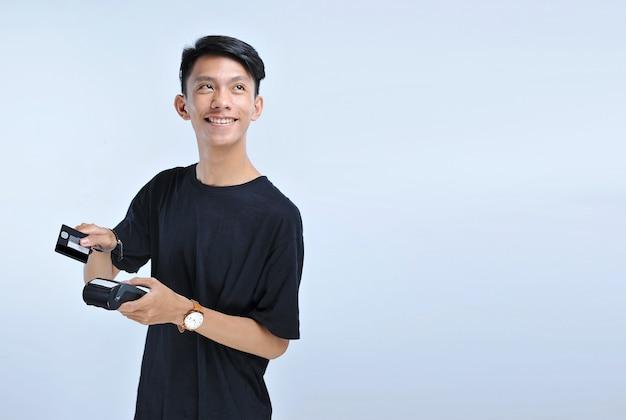Jonge aziatische man veegt een creditcard / een bankpas en kijkt naar de kopieerruimte geïsoleerd over de grijze achtergrond
