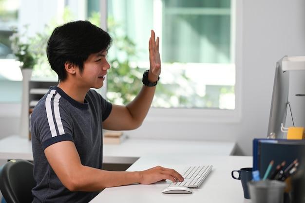Jonge aziatische man video-oproep met zijn collega zittend in zijn moderne huis