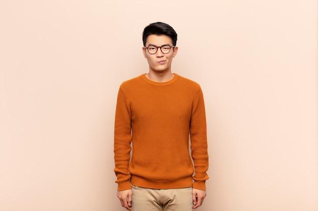 Jonge aziatische man voelt zich verward en twijfelachtig, vraagt zich af of probeert te kiezen of een beslissing te nemen over kleurenmuur