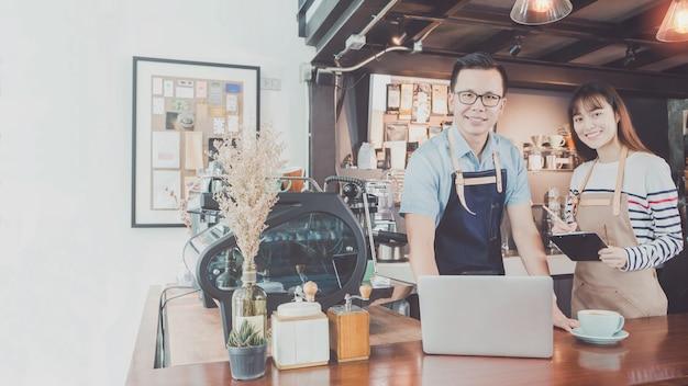 Jonge aziatische man & vrouw barista slijtage schort