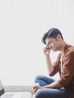 Jonge aziatische man wrijft in zijn ogen