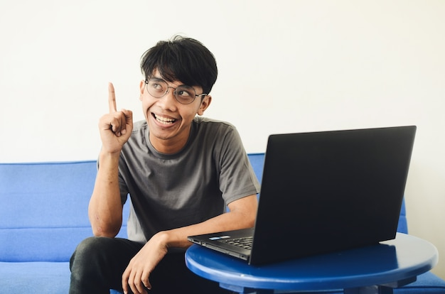 Jonge aziatische man zittend op de bank voor de laptop met een uitdrukking van het vinden van ideeën