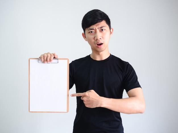 Jonge aziatische man zwarte hemd wijsvinger op houten klembord leeg document in de hand serieus gezicht