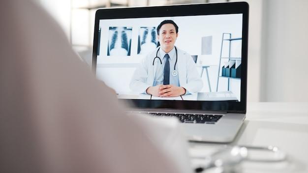 Jonge aziatische mannelijke arts in wit medisch uniform met behulp van laptop pratende videoconferentiegesprek met senior arts aan balie in gezondheidskliniek of ziekenhuis.