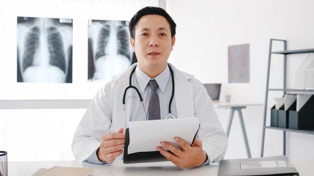 Jonge aziatische mannelijke arts in wit medisch uniform met stethoscoop met behulp van computerlaptop praat videoconferentiegesprek met patiënt, kijkend naar camera in gezondheidsziekenhuis.