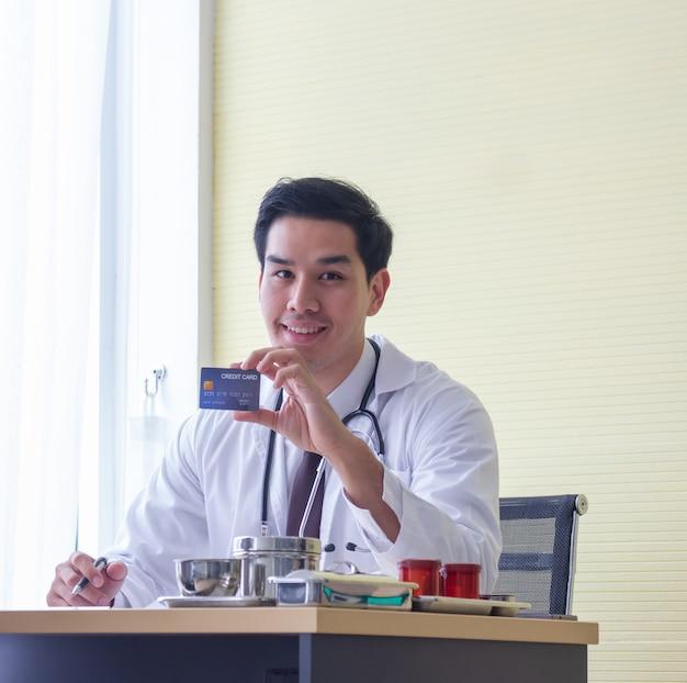 Jonge aziatische mannelijke artsenglimlachen die creditcard op bureau in het ziekenhuis tonen