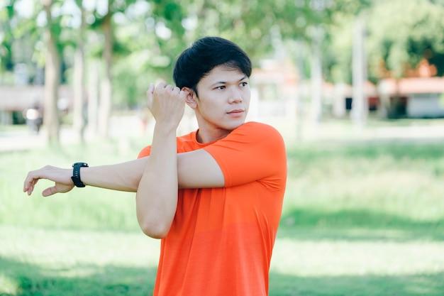 Jonge aziatische mannelijke jogger die opwarmt door armen en bovenlichaam te strekken voordat hij gaat rennen.